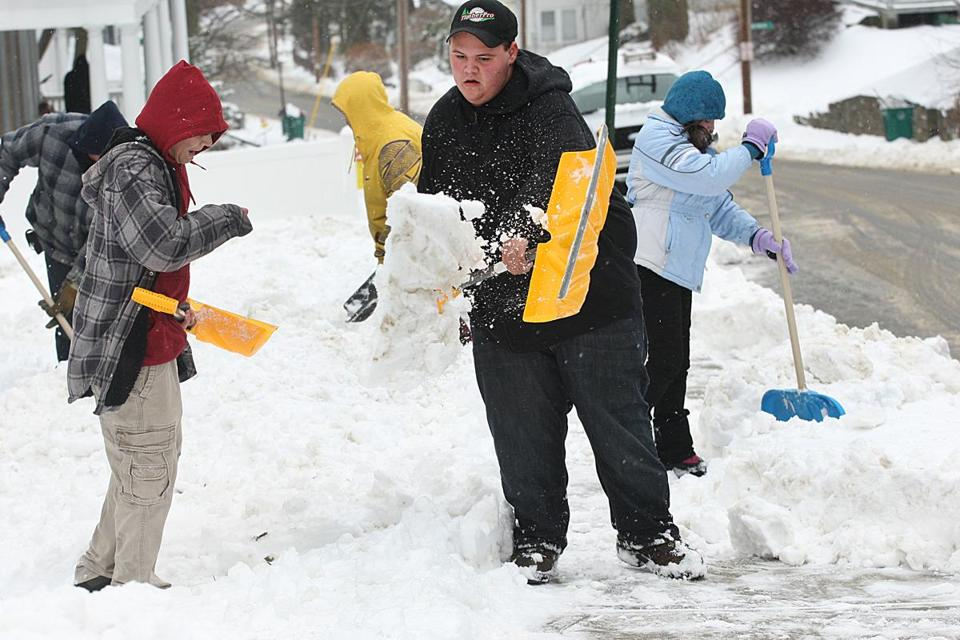 Sean Correa, 15, and family members cleared their sidewalk in Fitchburg on Thursday after the first winter snowstorm of the year struck Central and Western Massachusetts and Northern New England.
