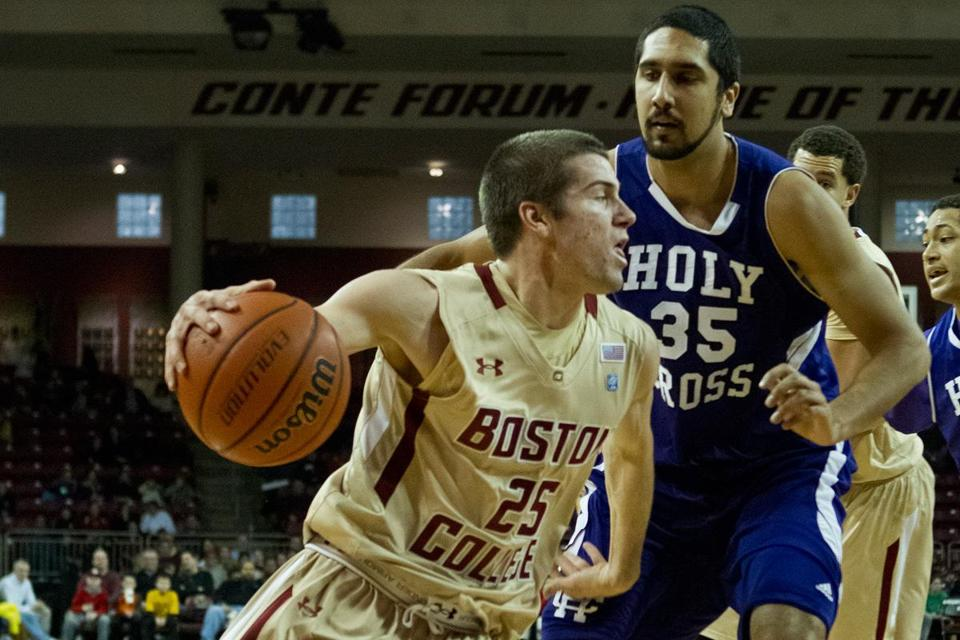 BC guard Joe Rahon (9 points) has a step on Eric Obeysekere of Holy Cross while driving during the first half.