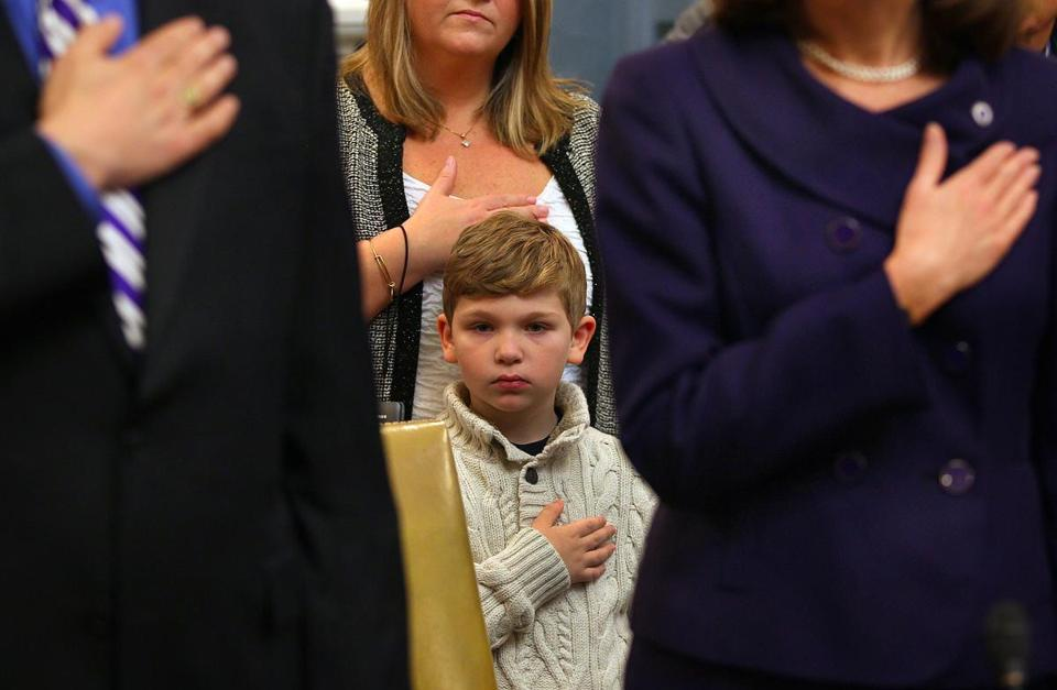 Matthew DiDomenico, 7, puts his hand over his heart during the pledge of allegiance at the swearing in ceremony for new Massachusetts State Senators. His father is State Senator Sal DiDomenico from Everett.