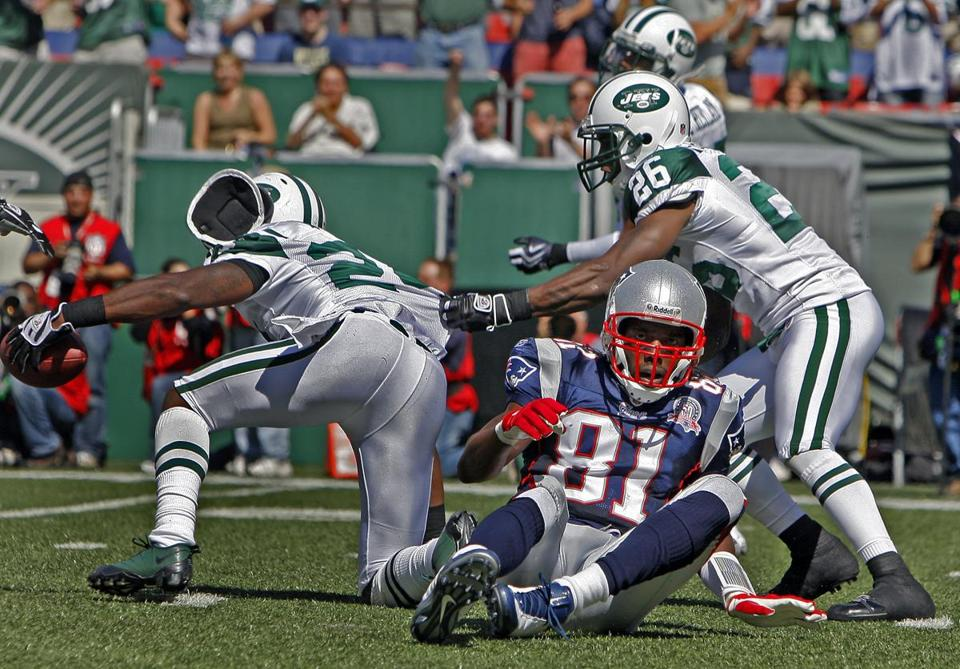 Randy Moss was left on the ground as Darrelle Revis intercepted Tom Brady in the first half.