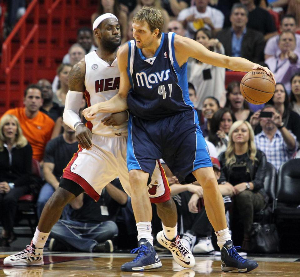 Dallas Mavericks' Dirk Nowitzki, right, drove against Miami Heat's LeBron James during the fourth quarter of their NBA basketball game, Wednesday, Jan. 2, 2013, in Miami. The Heat won 119-109 in overtime.