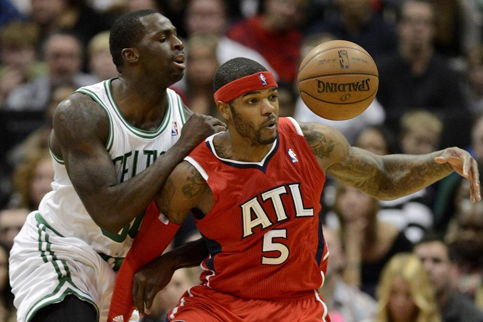 Brandon Bass of the Celtics and the Hawks' Josh Smith eye a loose ball during the first half.