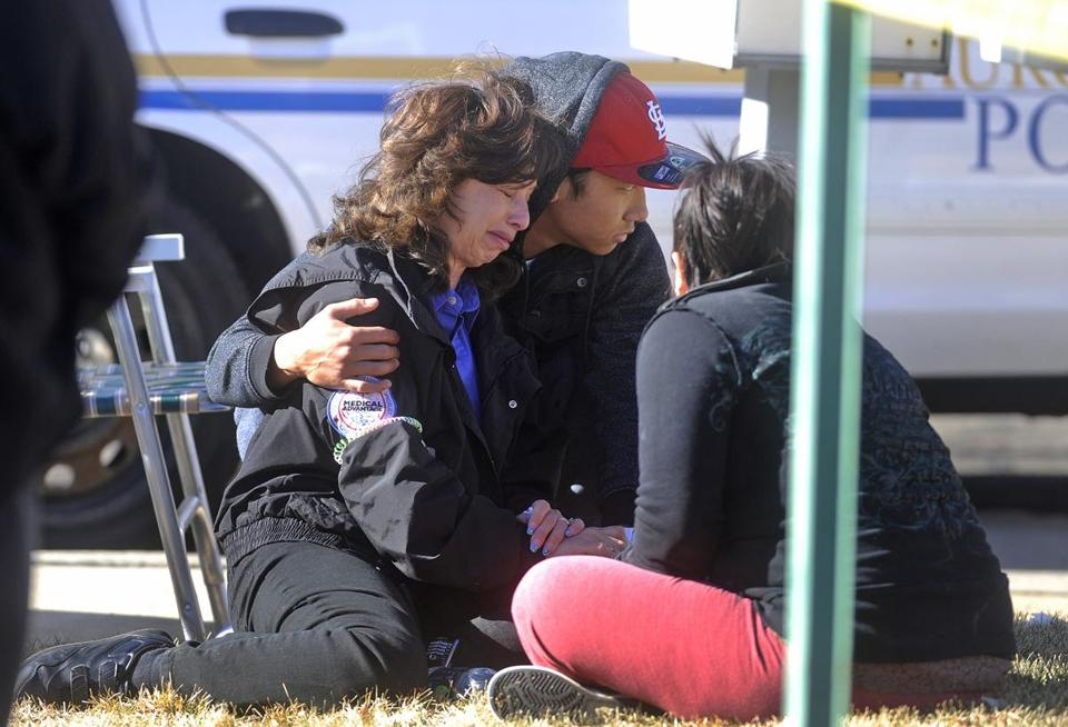 An unidentified woman was consoled outside a town-house complex following shootings in Aurora, Colo., Saturday.