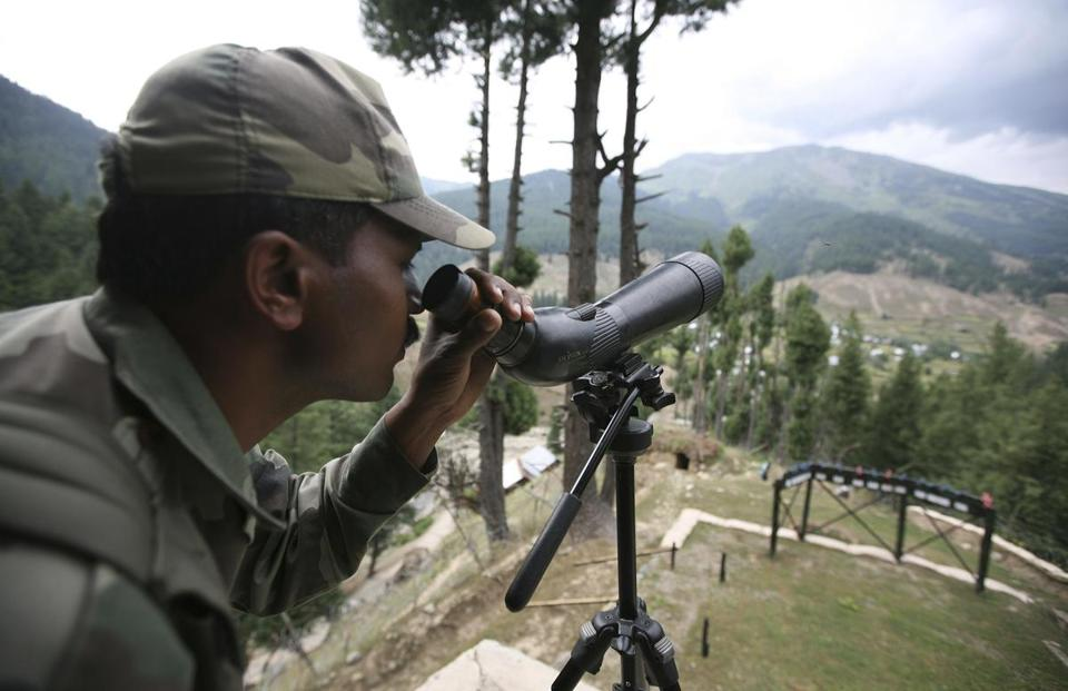 An Indian soldier looked through a spotting scope at a military camp north of Srinagar as troops battled gunmen in August 2011.