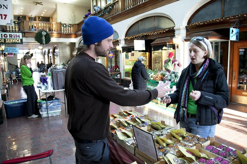 At Brookline's winter market, Jenn Engstrom buys a bag of Mexican chocolate almonds early this month from Eric Doyle of Q's Nuts. She just moved to Brookline from Michigan and happened upon the market.