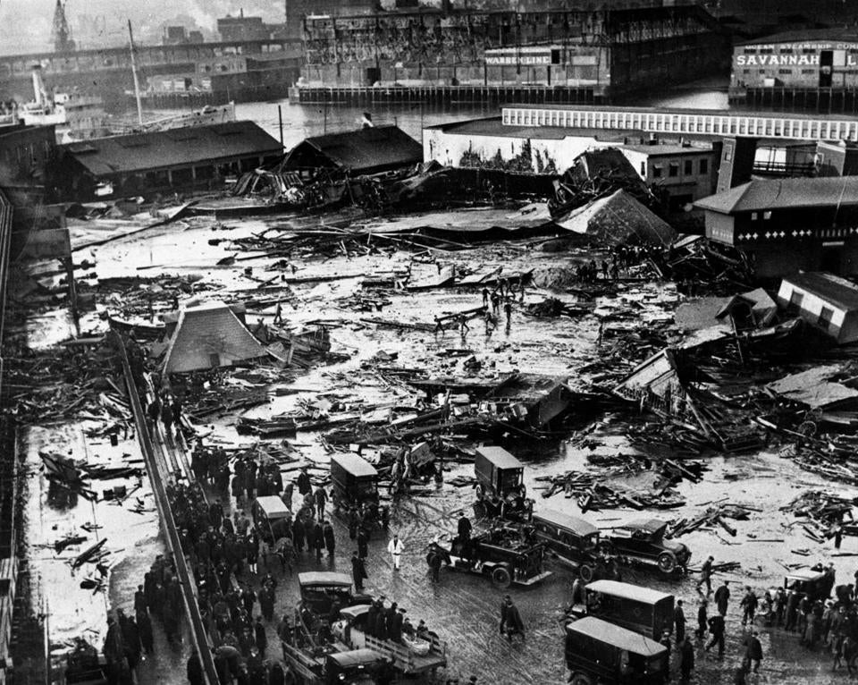 January 16, 1919: On January 15, 1919 at approximately 12:40 pm the North End was shaken by a terrific explosion caused by the bursting of a giant tank at the Purity Distilling Co. on Commercial St. This a view of the aftermath looking north across North End Park. The great molasses tank was located in the center of this picture. Sections of the metal may be seen blown to the extreme left and right in the picture. Twenty-one people perished, including two ten-year-old children, Pasquale Iantosca and Maria Distasio, who were collecting firewood near the molasses tank while home from school for lunch.