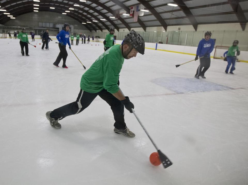 A broomball game recently played at Reilly Memorial Rink in Brighton. Instead of skates, the game is played in sneakers with participants running on the ice.