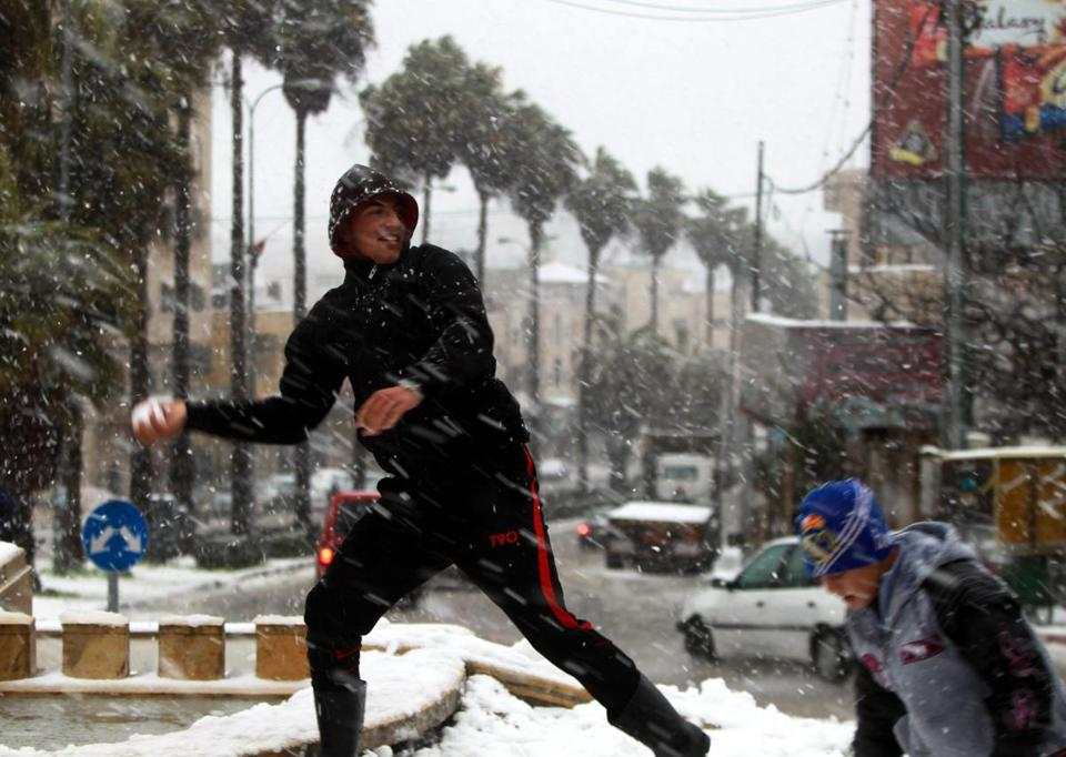 Palestinians in the West Bank city of Hebron played in snow on Wednesday as the fiercest winter storm to hit the Middle East in years caused eight deaths and widespread disruption in the region.