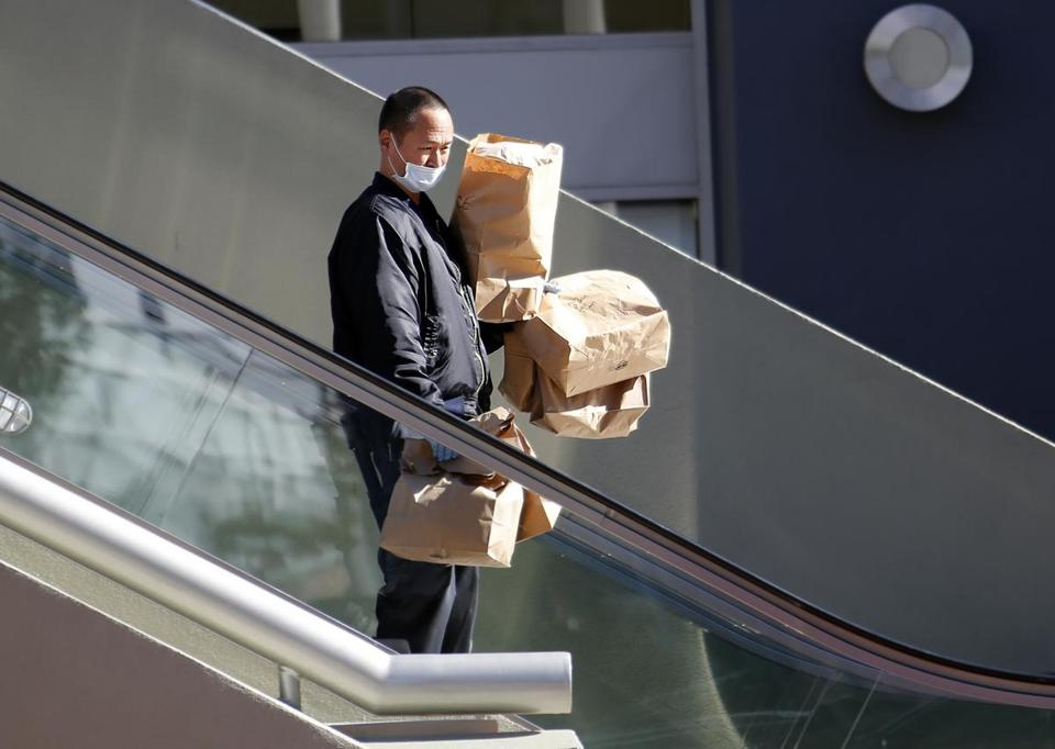 A police investigator carried evidence bags from a Nordstrom Rack store at the Howard Hughes Center.