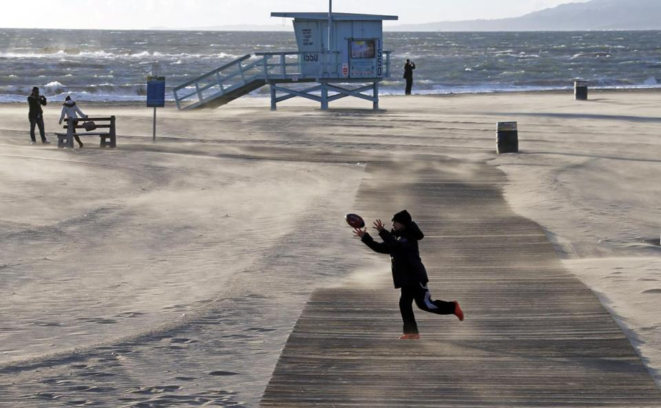 Bundled up against the elements, a boy played on a nearly deserted beach at Santa Monica, Calif., on Thursday.