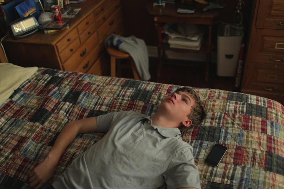 "Miles Heizer plays a shy teenager in a texting romance in ""The Arm."""