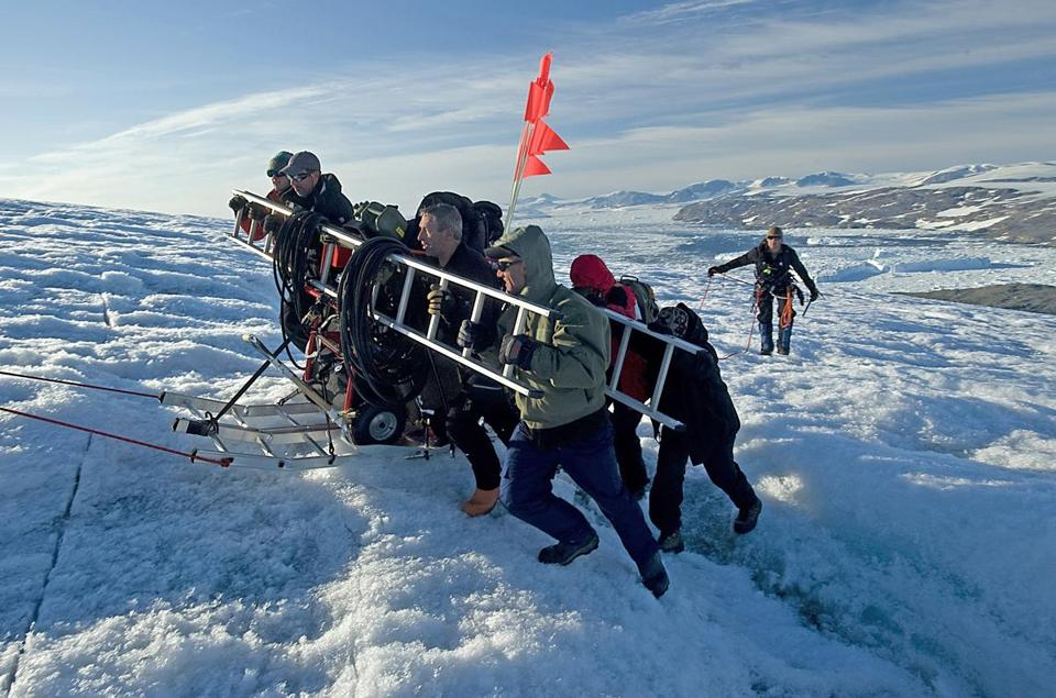 The expedition team of service members, explorers, and scientists from the Coast Guard and North South Polar Inc. transported equipment over a crevasse near Koge Bay in Greenland.