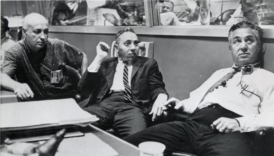 D. Brainerd Holmes (center) and other Mercury program directors took a break after Gordon Cooper circled Earth.
