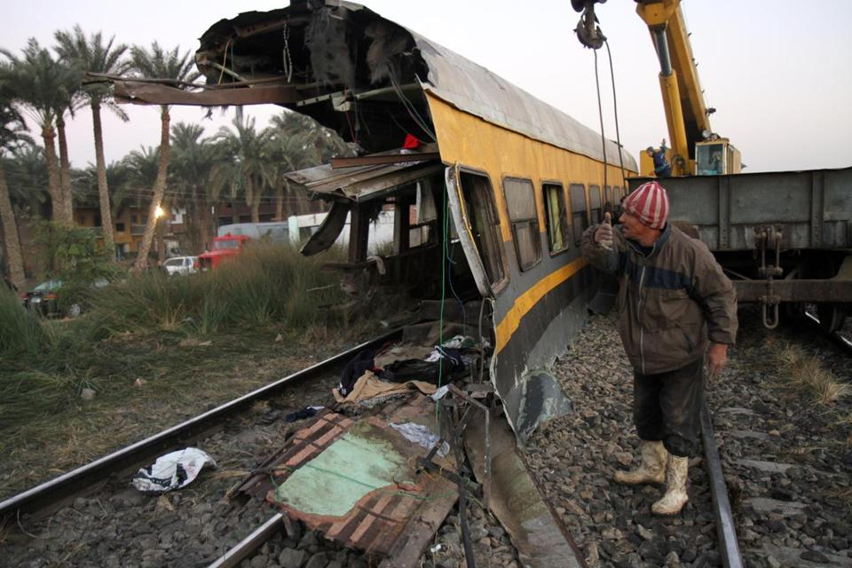 Egyptian railway workers attempted Tuesday to remove debris from tracks following a train crash in Badrasheen, south of Cairo. Some 1,300 military recruits were aboard.