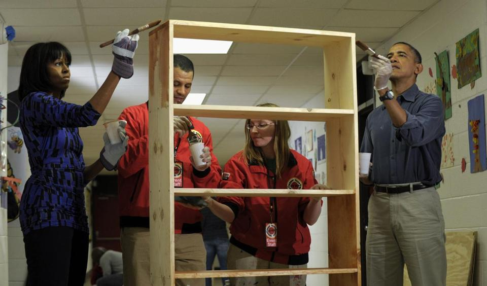 President Barack Obama and first lady Michelle Obama stained a bookshelf at Burrville Elementary School in Washington, Saturday, as the the first family participated in a community service project for the National Day of Service, part of the 57th Presidential Inauguration.