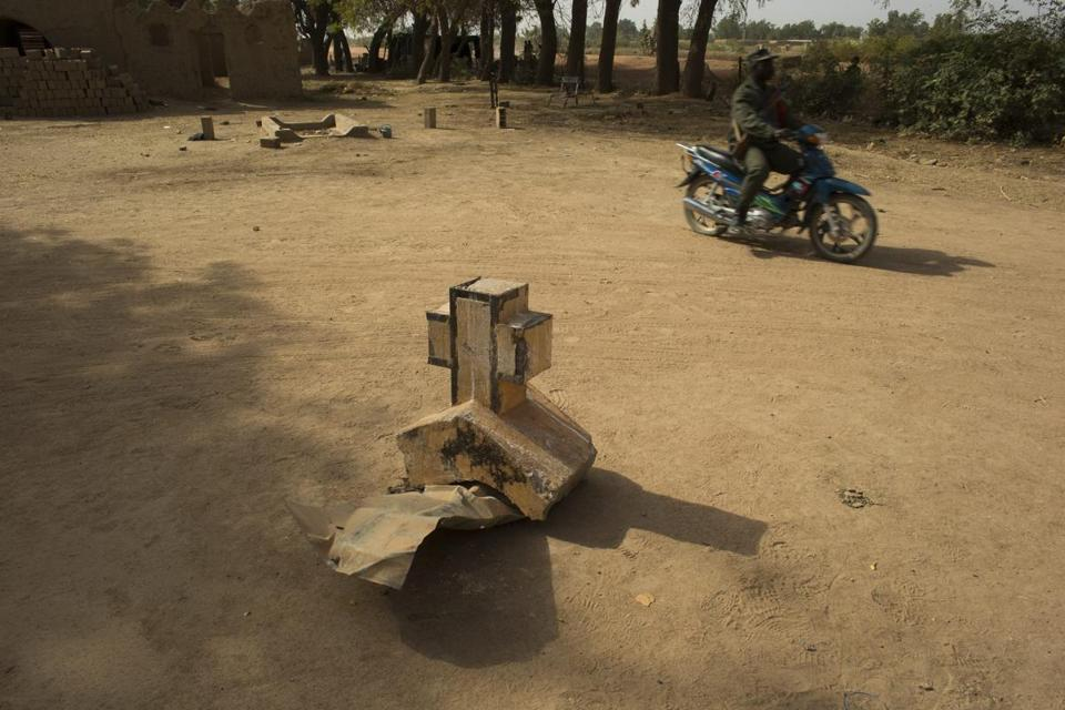 A soldier rode past a cross from a church ransacked by Islamic militants in Diabaly, Mali.