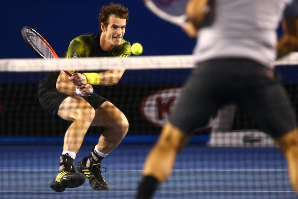 Andy Murray backhands a return during his first career victory over Roger Federer in a Grand Slam event.