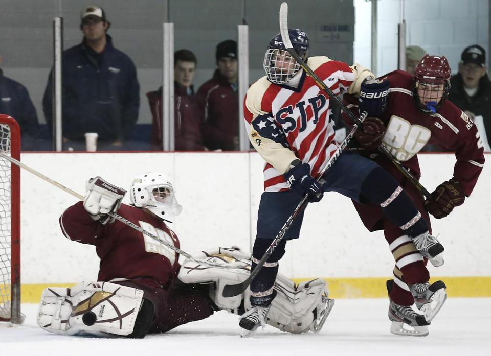St John Prep's Andrew Brandano (center) tries to shake off Billy Roche while looking for a rebound in front of BC High goalie Peter Cronin.