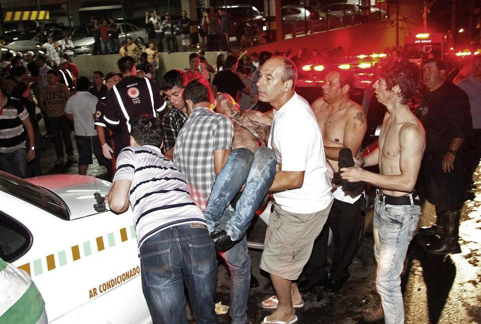 Residents helped evacuate injured victims after a nightclub fire in Santa Maria, Brazil, early Sunday. The blaze was ignited by pyrotechnics during a rock band's performance, authorities said.