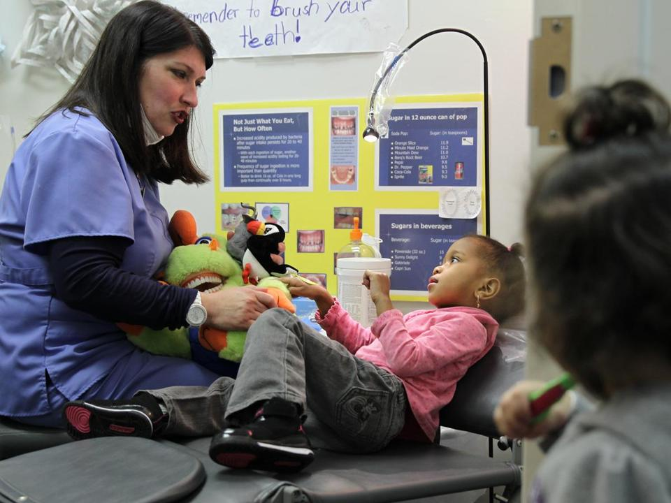 Carol Gilmore, a public health hygienist who provides dental services to children, treats Kyara Fortes at the offices of Brockton Area Multi-Services Inc.