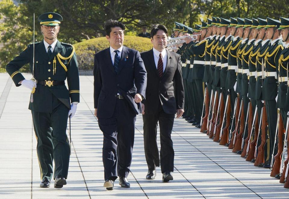 Japan's Prime Minister Shinzo Abe, center, and Defense Minister Itsunori Onodera review an honor guard before a flag return ceremony last week.