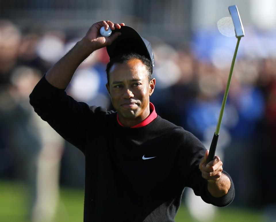 In what has become old hat at Torrey Pines, Tiger Woods tips his cap after winning at the famed course, his 75th victory on the PGA Tour.