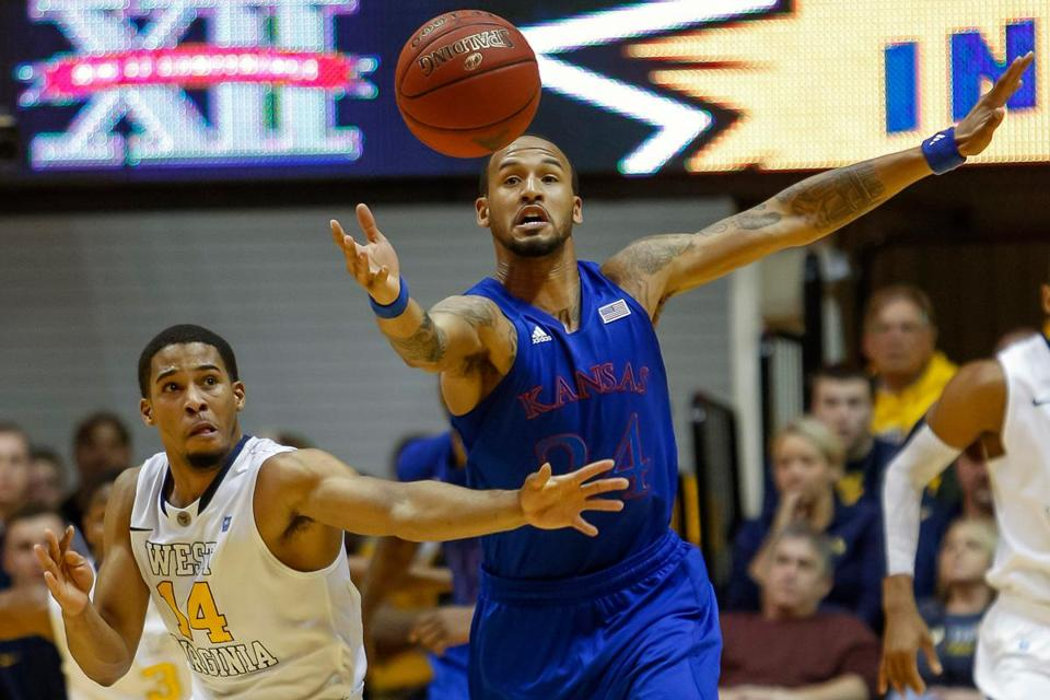 Travis Releford of Kansas (right) looks to have the inside track on West Virginia's Gary Browne for a loose ball.