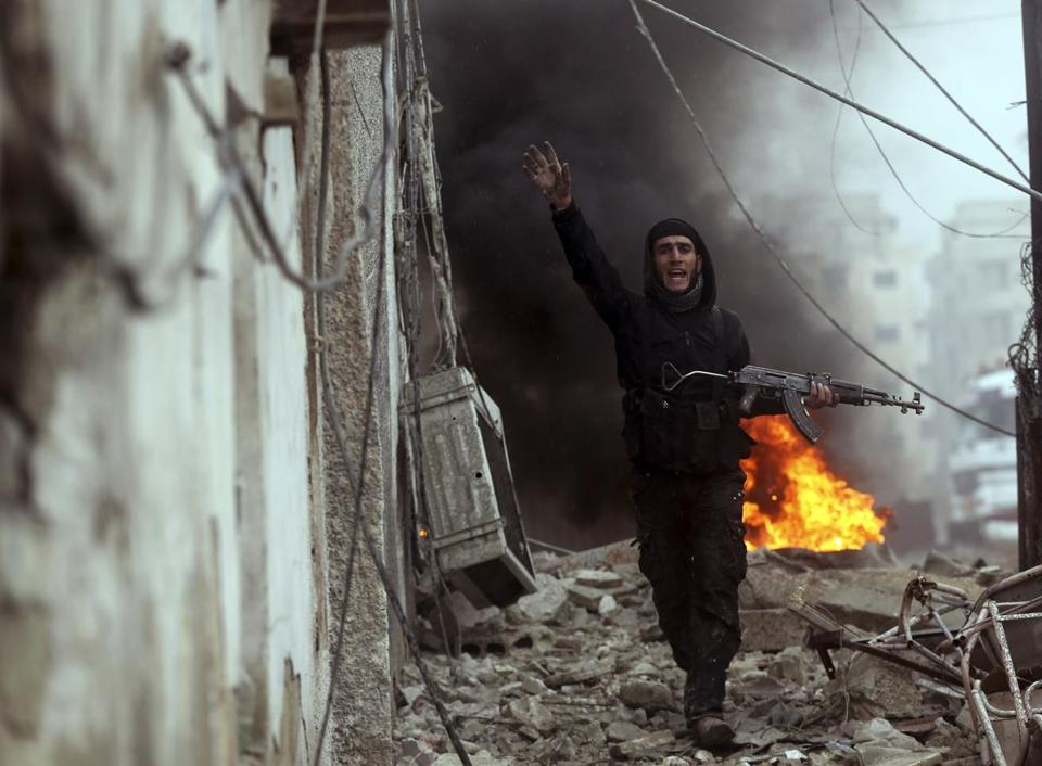 An opposition fighter gestured near a barricade during fighting in the Ain Tarma neighborhood of Damascus Wednesday.
