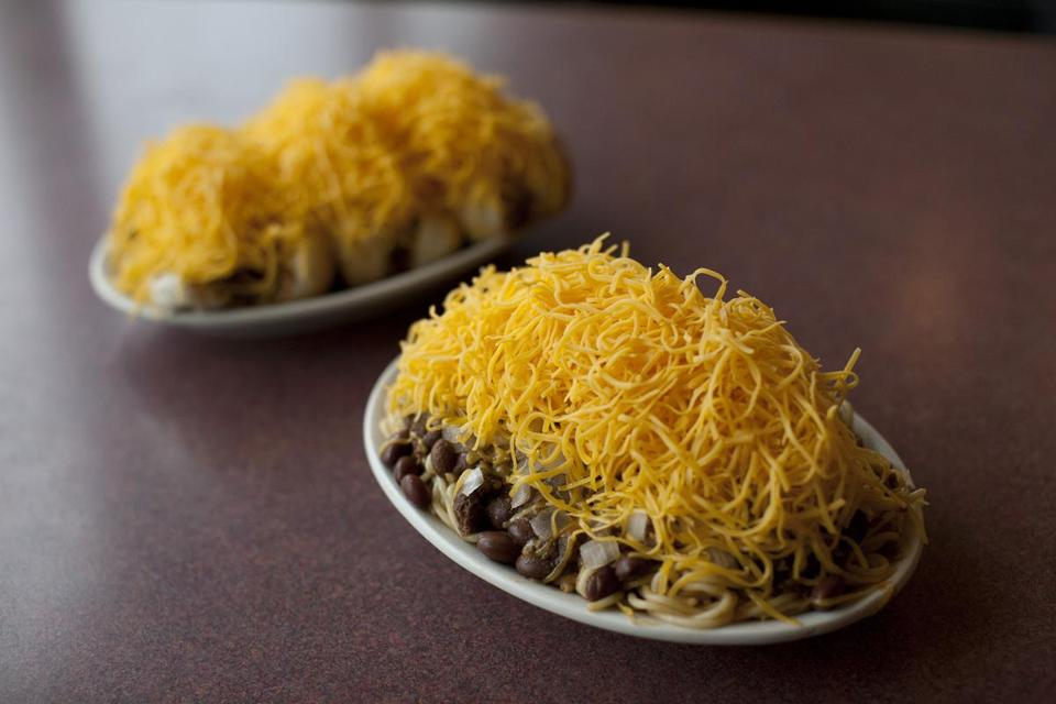 "Shredded cheese blankets a plate of Coneys and a ""five-way."""