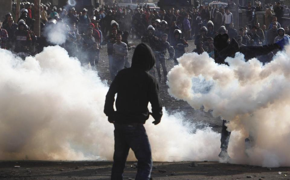 Protesters threw tear gas canisters back to riot police during one of several clashes in Cairo on Tuesday.