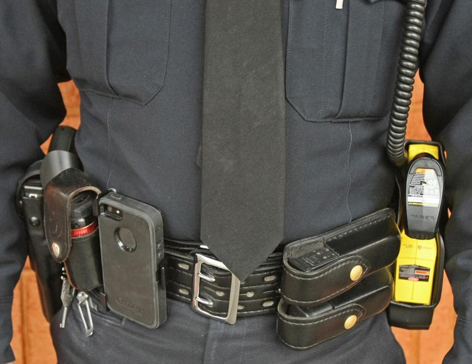 A Stoughton police officer's belt carries a department-issue standard firearm to the left, and a Taser electroshock device to the far right.