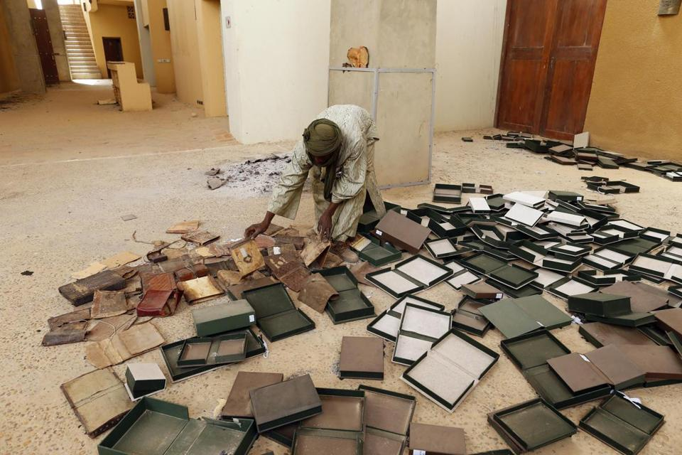 A museum guard picked through ancient manuscripts, which were partially damaged by Islamist rebels before they fled Timbuktu. Most of the texts appeared to be safe.