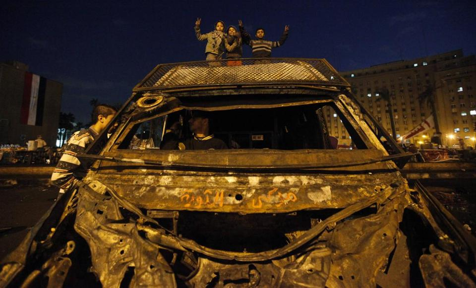 Protesters opposing Egypt's leader, Mohammed Morsi, stood on a police vehicle seized in clashes with Cairo riot police.