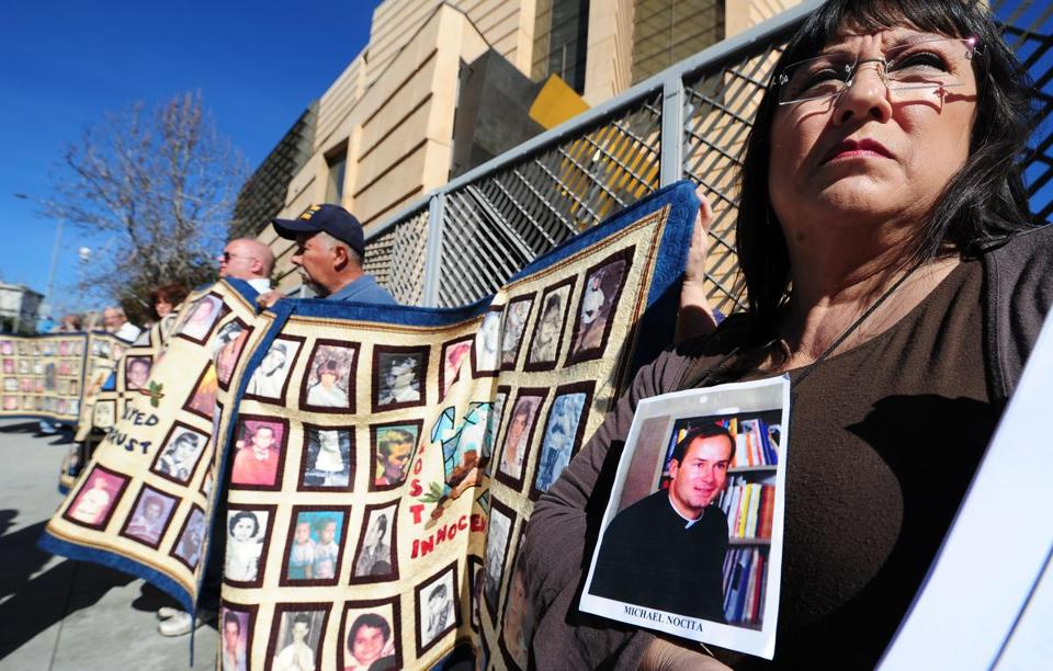 Victims and supporters held quilts with portraits of abused children outside the Cathedral of Our Lady of the Angels.