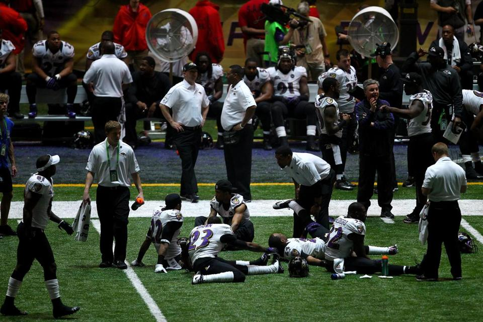 Ravens players limber up during the 34-minute power outage at the Superdome that was a Super Bowl first.