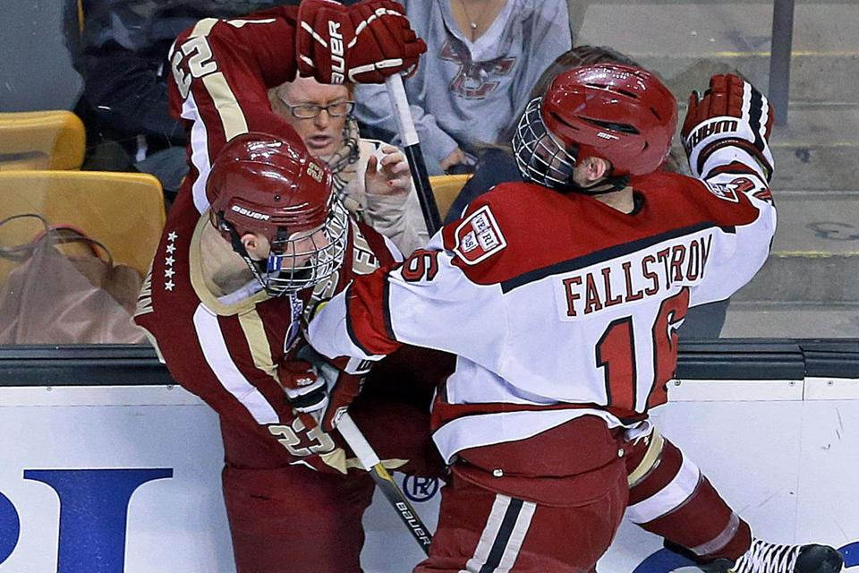 Sticks are breaking and a fan is bracing as BC's Patrick Brown and Harvard's Alex Fallstrom collide.