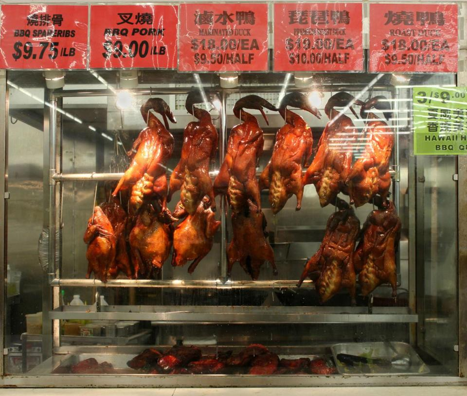 The traditional Asian fare on display at Kam Man Food in Quincy includes (clockwise, from left) roasted ducks, whole fresh fish, and dragonfruit, which is particularly popular during Chinese New Year celebrations since red and pink are considered to be lucky colors.