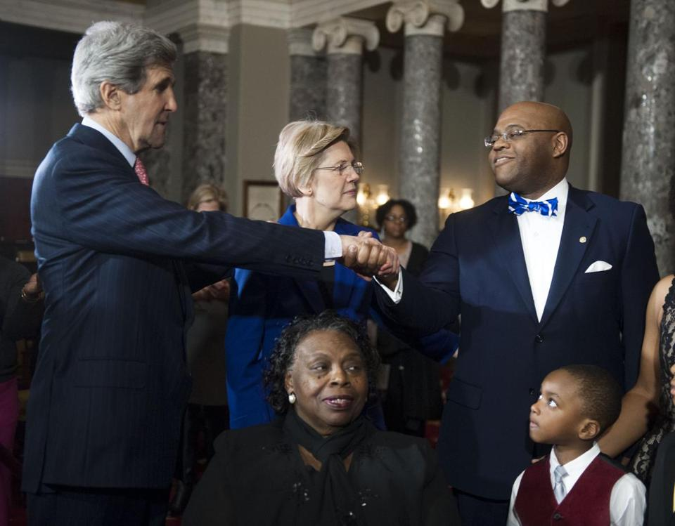 "Senator William ""Mo"" Cowan was congratulated by Secretary of State John F. Kerry as Senator Elizabeth Warren, Cowan's mother, Cynthia, and his son Miles looked on."