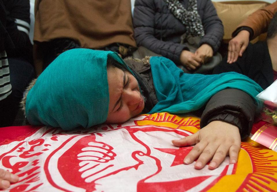 A relative of Chokri Belaid cried on his coffin in Tunis on Thursday. The opposition leader was assassinated Wednesday.