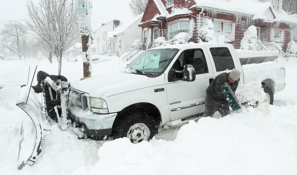 Larey Rose (left) and Michael Gelard tried to dig out their snow plow after it got stuck in deep snow Saturday in Providence.