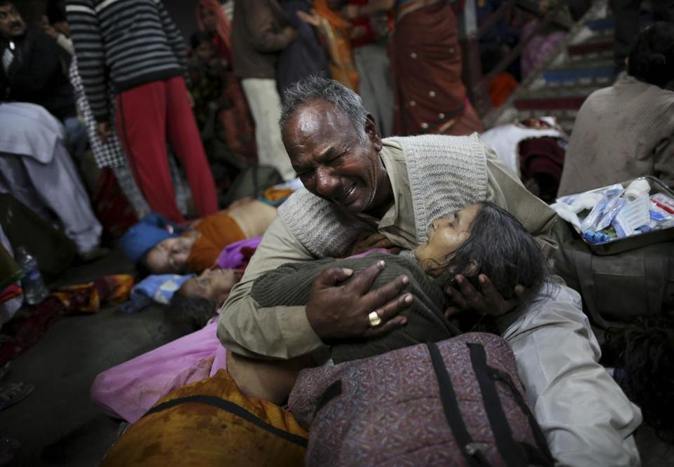 An Indian man wept as he held his wife, who was killed in a stampede at the main railway station in Allahabad, India.