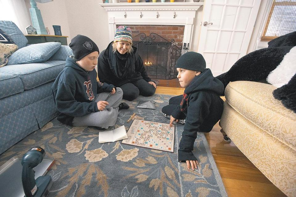 Amy Kelly and her sons, John, 12, (left) and Matthew, 9, dressed warmly to play a board game Saturday after losing power Friday night.