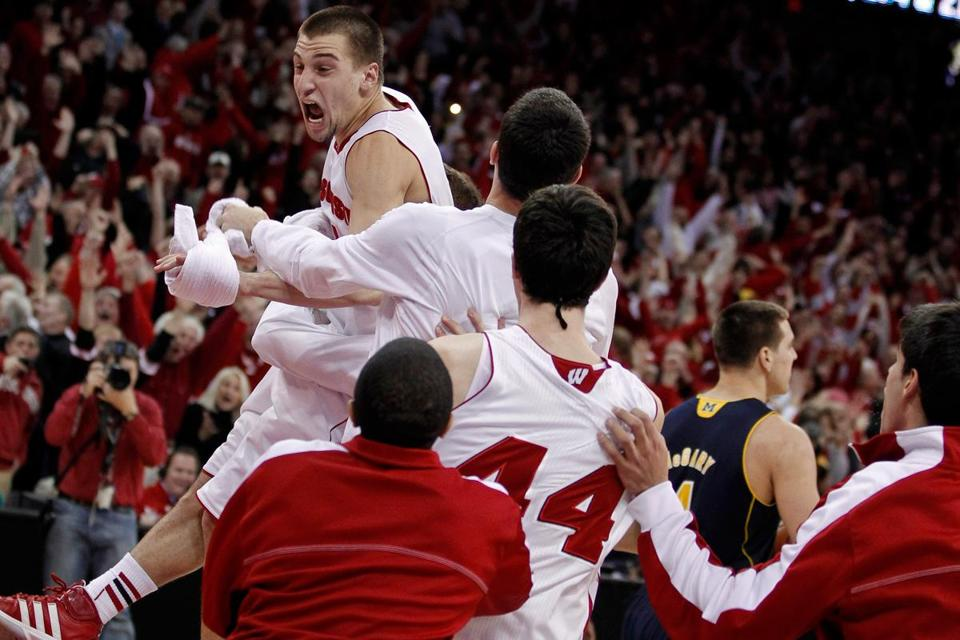 Wisconsin's Ben Brust is mobbed by teammates after his halfcourt shot forced OT.