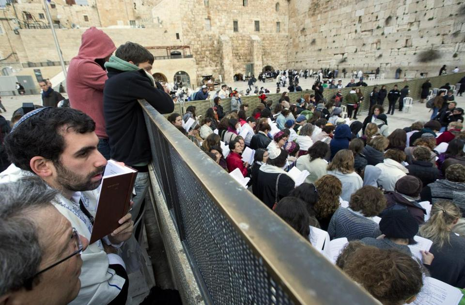 An Israeli man in his prayer shawl watched a large group of women gather Monday at the Western Wall in Jerusalem.