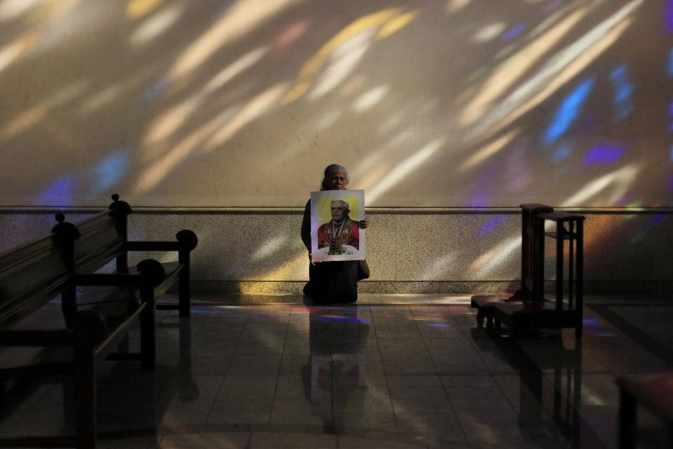 A kneeling Adelina Hidalgo held a picture of Pope Benedict XVI in the Metropolitan Cathedral in San Salvador.