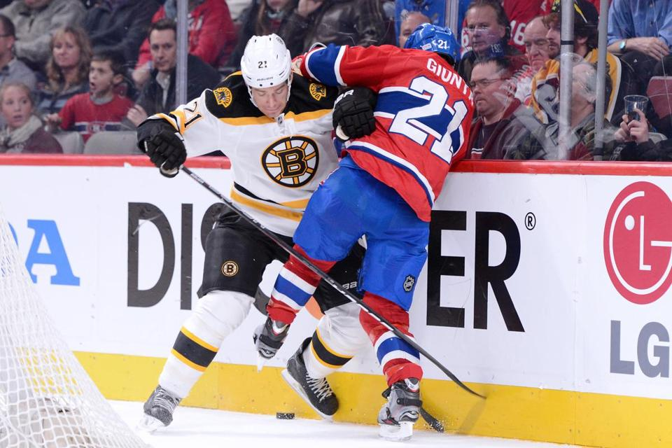 Andrew Ference of the Boston Bruins and Brian Gionta of the Montreal Canadiens battle for the puck during the NHL game at the Bell Centre on February 6, 2013 in Montreal, Quebec, Canada. The Bruins defeated the Canadiens 2-1.