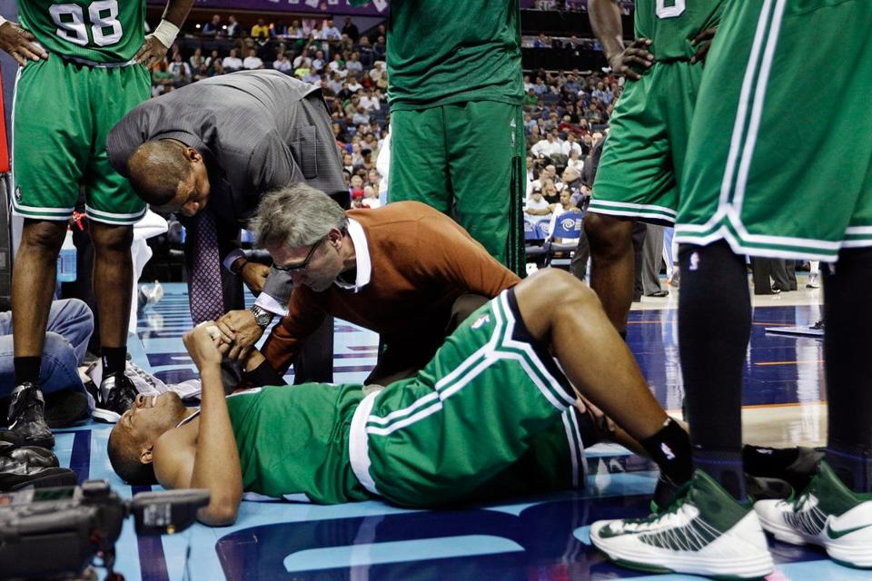 Guard Leandro Barbosa is tended to by coach Doc Rivers and trainer Ed Lacerte after injuring his left knee.