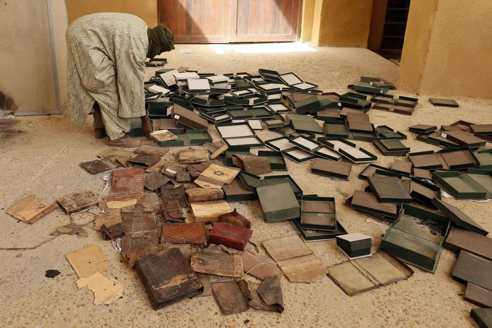A museum guard works around boxes that held ancient manuscripts that were partially damaged when rebels set fire to the Ahmed Baba Institute.