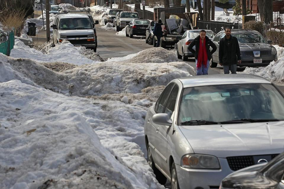 Piles of snow blocking parts of Perrin Street forced people into the roadway Wednesday, a situation seen in other parts of the city, too.