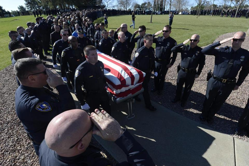Riverside police officers saluted the casket of Officer Michael Crain in California. He was a victim of Christopher Dorner.